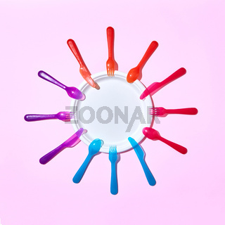 Multicolored plastic utensil around white plate on pink.