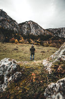 man is standing near a forest in the mountains during autumn