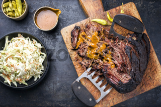 Traditional barbecue wagyu pulled beef with coleslaw and spicy sauce as top view on a rustic cutting board