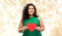 happy woman holding red heart over lights