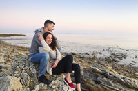 Young couple at rocky seacoast in sunset