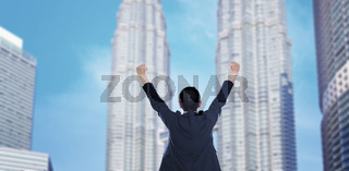 Business success - Celebrating business man overlooking the city center high-rises.