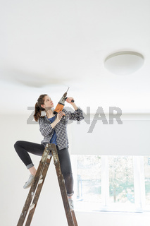 Frau als Heimwerker mit Bohrmaschine auf Leiter