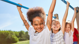 Multikulturelle Kinder hangeln an Klettergerüst