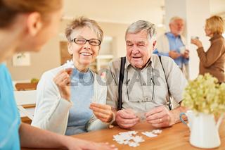Senioren Paar beim Puzzle spielen im Seniorenheim