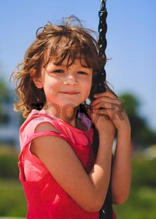 Mädchen auf Eisenkettenschaukel schaut in die Kamera
