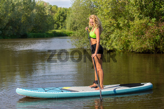 Standing caucasian woman paddling with SUP