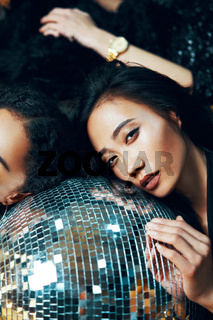 Pretty woman relax and lying down on the floor on disco ball in nightclub after crazy party