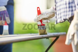 Hände mit Pinsel beim streichen von Holztisch