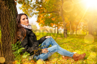 Beautiful romantic girl in a park autumn scenery looking at the camera, sitting down next to a tree, enjoying the perfect weather in a sunny day. Gorgeous young woman outdoors. Full length body shot