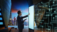 Smart businessman touch the screen to search the information of intelligent communication network of things . Night scene with modern city background .