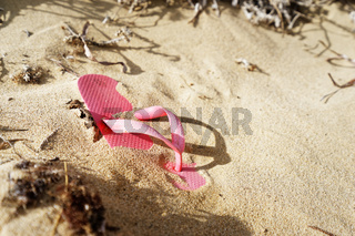 Flipflop als Strandgut am Sandstrand