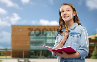 teenage student girl with notebook over school