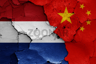 flags of Netherlands and China painted on cracked wall