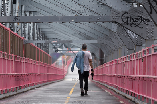 Rear view of unrecognizable stylish young man carrying jeans jacket over his shoulder walking on Williamsburg Bridge, Brooklyn, New York City.