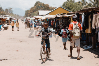 Young boy riding bicycle on street. Madagascar