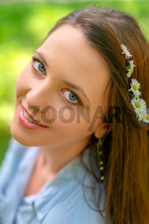 Young beautiful girl with perfect skin and makeup is posing in a spring park scenery, looking at the camera. Gorgeous woman outdoors enjoying nature. Healthy smiling girl over a green background