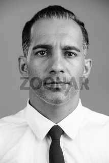 Face of mature handsome Persian man in black and white
