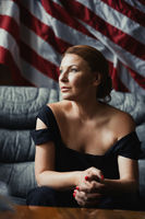 Stylish woman sitting on a sofa against of the American flag.