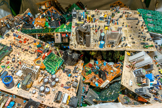 Electronic circuit boards from used television sets waiting to be recycled on a recycling plant site. Sorted electronic garbage.