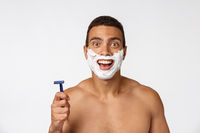 Close up of a happy naked african man with face in shaving foam holding razor isolated over gray background.