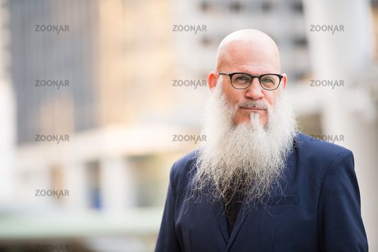 Mature bearded bald businessman in the city outdoors