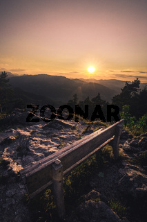 Wooden bench seat on top of the mountain during the beautiful and vibrant sunset.