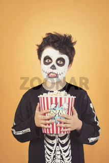 Happy Halloween.funny child in a skeleton costume with popcorn