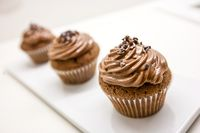 Chocolate cupcakes on white plate and table