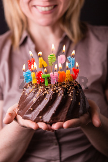 Mother holding a birthday cake with colorful candles. Birthday