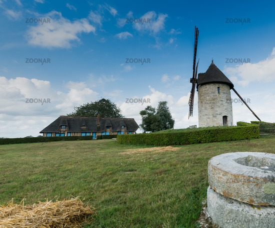 view of the historic windmill Moulin de Pierre and old millstones in Hauville in Normandy