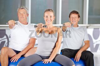 Senioren trainieren mit Hanteln im Fitnesscenter