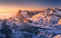 Aerial view of snowy mountains, blue sea and orange sky at sunset