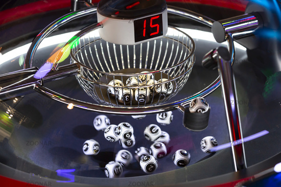 Black and white lottery balls in a rotating bingo machine. Number 15