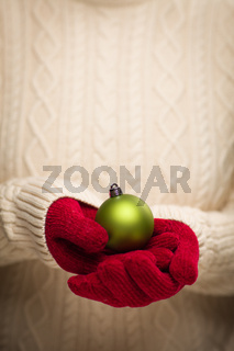 Woman Wearing Seasonal Red Mittens Holding Green Christmas Ornament