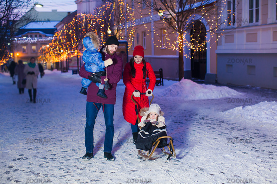 Beautiful family during winter walk with city background