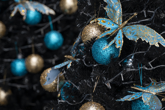 Decorated Christmas tree with a blue and gold toys and beautiful blue butterfly toy. Holidays. Preparation for New Year and Christmas.