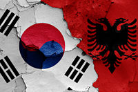 flags of South Korea and Albania painted on cracked wall