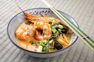 Traditional Thai kaeng phet red curry with king prawns and vegetable as top view in a bowl on place mat