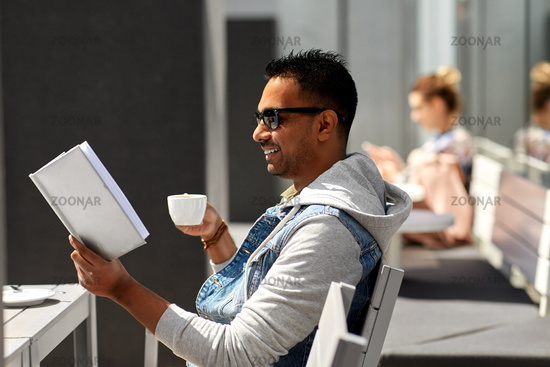 man reading book and drinking coffee at city cafe
