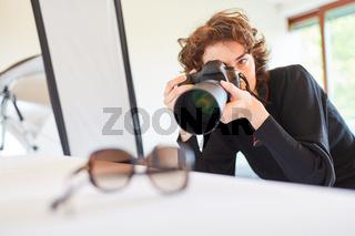 Fotografin mit Kamera fotografiert Brille