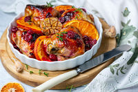 Chicken thighs baked with orange and cherry.