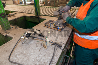 Bucharest, Romania - October, 2013: Workers disassembling electronic components of used television sets and preparing them to be recycled on a recycling plant