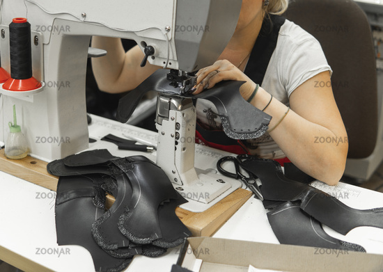 Sewing machine in a leather workshop in action with hands working on a leather details for shoes. Women's hands with sewing machine at shoes factory.