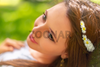 Young beautiful girl with perfect skin and makeup is posing in a spring park scenery. Gorgeous woman outdoors enjoying nature. Healthy smiling girl over a green background. Head shot in natural light