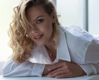Gorgeous sexy blonde lying on window sill portrait