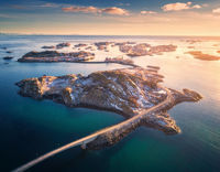 Aerial view of bridge over the sea and snowy mountains