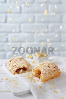 Almond flakes falling from above over caramel strudel