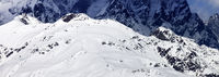 Panoramic view on sunlit snowy mountains at winter