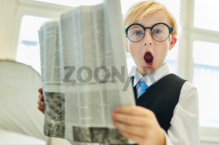 Junge als staunender Geschäftsmann beim Lesen